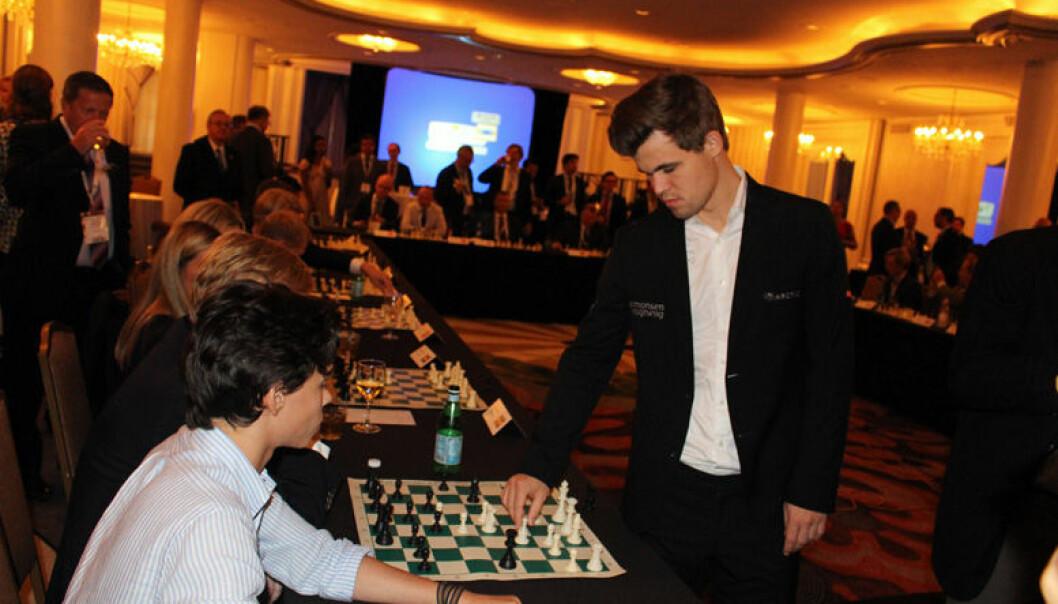 Magnus Carlsen gikk fra bord til bord under seansen på Omni Shoreham hotel. Her flytter han en brikke på brettet til Norges ambassadør Kåre R Aas som for anledningen hadde tatt med seg sønnen Felipe på sitt lag.