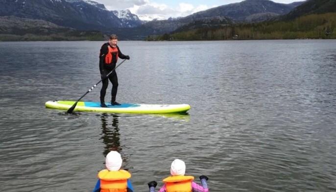 Brettpadling på Vatnevatnet utenfor Bodø med tvillingene Thea og Teodor som tilskuere.