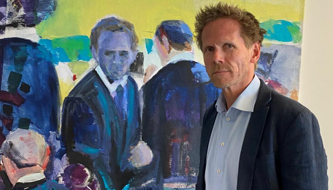 Fredrik Sejersted foran et maleri der han selv figurerer, malt av en ansatt hos Regjeringsadvokaten.